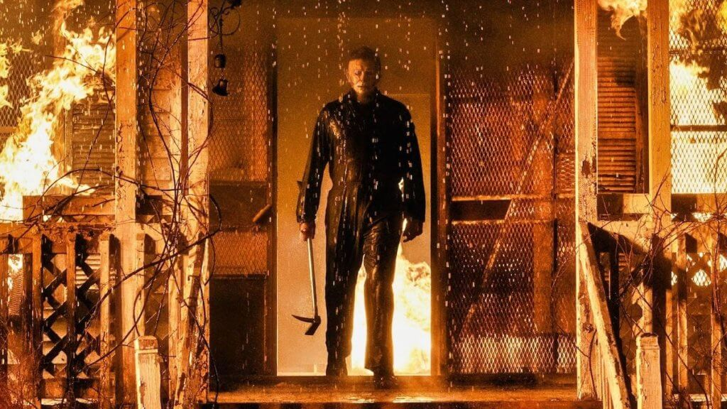 killer michael myers standing on porch of burning house